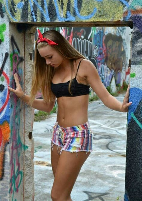 young girl models shorts she s trying to blend in with the colourful graffiti but