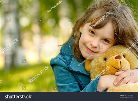 small beautiful pics small beautiful girl embraces an amusing bear cub against summer nature stock photo 21312358
