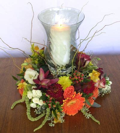 fall wreath centerpiece surrounds a hurricane lantern and