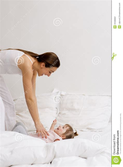 mother playing with son on bed in bedroom stock photo mother and daughter playing on the bed royalty free stock
