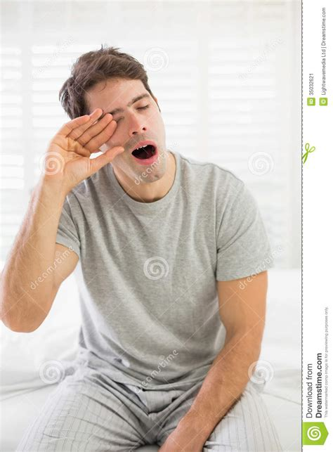 Hous Eplans by Sleepy Man Yawning As He Rubs His Eye In Bed Stock Image