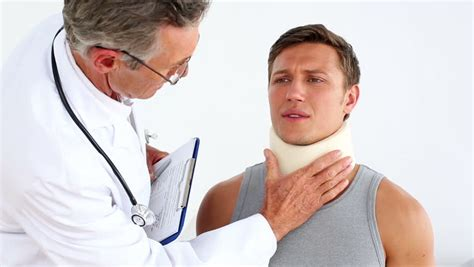 Rehab Doctors by Sportsman In Neck Brace Speaking To Doctor At The