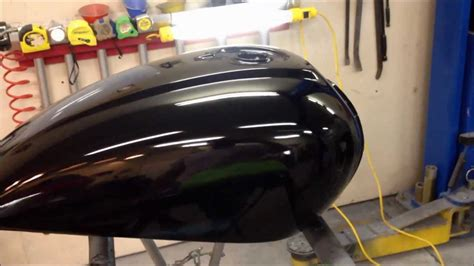 spray painting motorcycle finishing a paint on motorcycle a gas tank at the ugg
