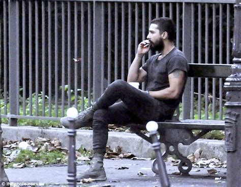 park bench actor shia labeouf cuts a lonesome figure smoking a cigarette on