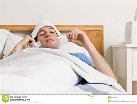 man with fever laying in bed taking temperature royalty
