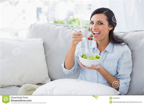 woman eats couch cheerful woman relaxing on the sofa eating salad royalty