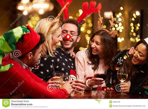 group of friends enjoying christmas drinks in bar stock