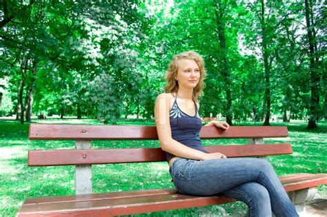 girl sitting on a bench young caucasian teen girl sitting on park bench stock