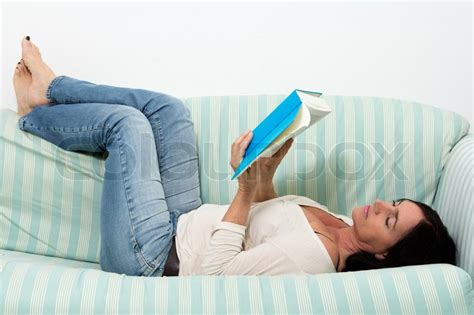 lie on couch dark haired woman lying on couch and reading a book
