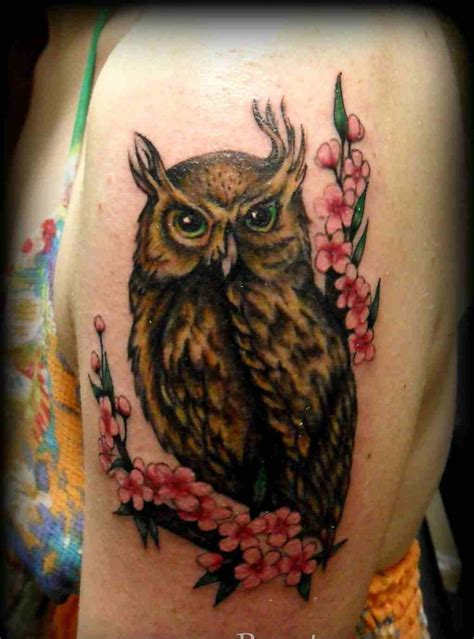 horned owl sitting on blossom branch tattoo on biceps jpg