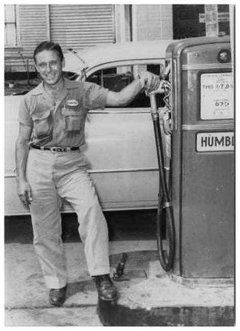 photograph of a humble gas station attendant standing next