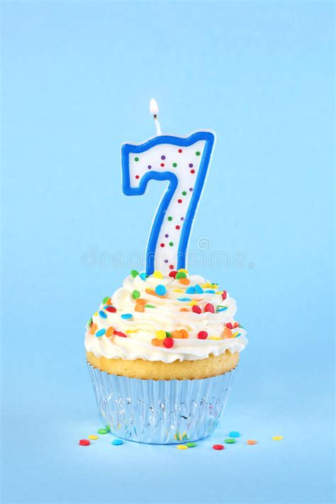iced birthday cupcake   lit number  candle stock