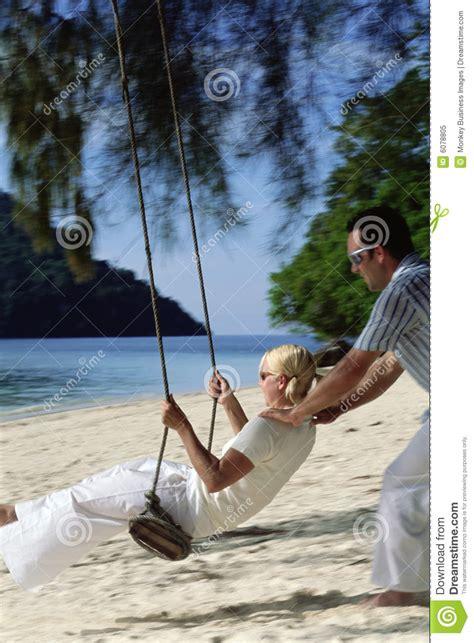 swing man man swinging woman on swing at beach royalty free stock