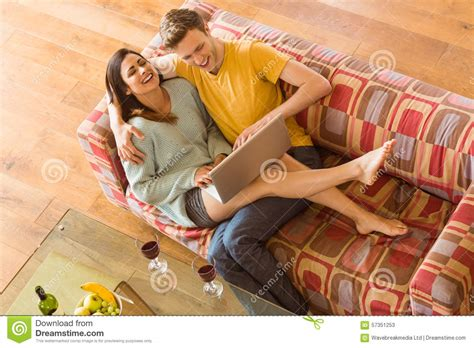 cuddling on the couch young couple cuddling on the couch with laptop stock photo
