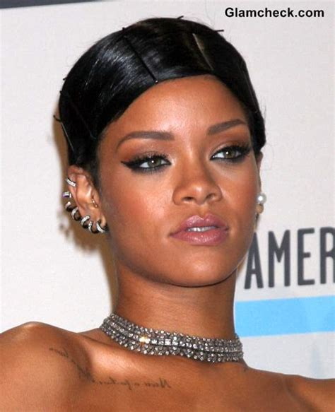 rihanna in silver diamond accessories and graphic tattoos