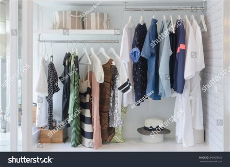 Hanging In Closet by Clothes Hanging In Closet With Hat At Home Stock Photo