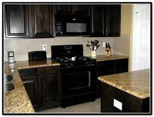 Dark brown kitchen cabinets with black appliances