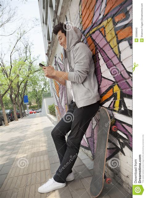 young man leaning   wall covered  graffiti