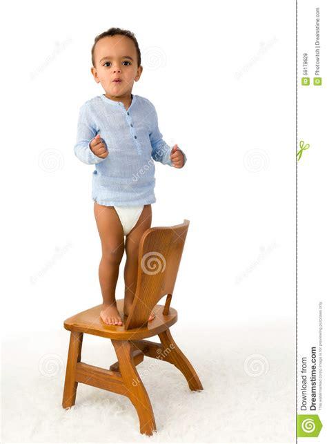 sulla sedia bambino che sta sulla sedia fotografia stock immagine