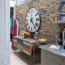 Distressed colourful sideboard complements this exposed brick wall