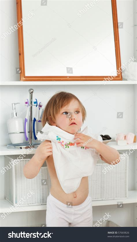 a girl using the bathroom small girl changing clothes in the bathroom stock photo