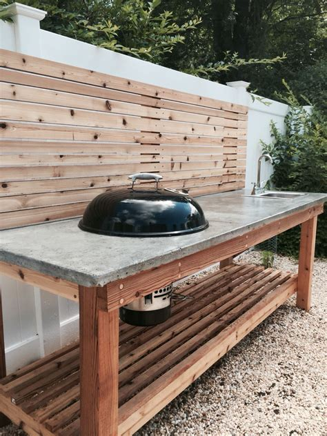 cedar wood outdoor kitchen with a concrete countertop and built in weber charcoal grill and sink