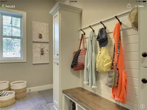 Shiplap wall with hooks in mudroom. More rustic bench with