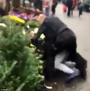 shopper fights three police officers among christmas trees
