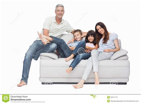 the couch people family sitting on sofa smiling at camera royalty free
