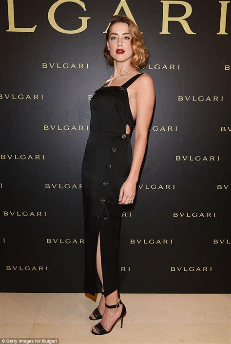 heard wears a curve hugging black dress at bulgari