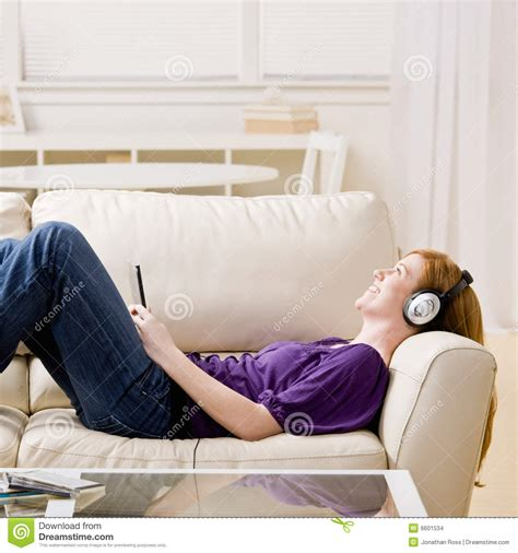 laying couch woman laying on sofa listening to music stock images