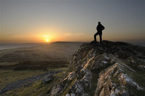 man standing on mountain top success time