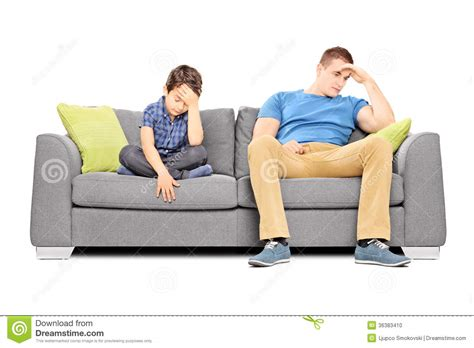 couch sitting dissappointed brothers sitting on a sofa stock photo