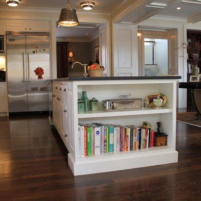 bookshelf at the end of the island for cookbooks i