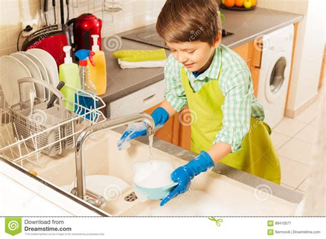 washing baby in kitchen sink boy wash dish in sink water from tap stock image image 89410577