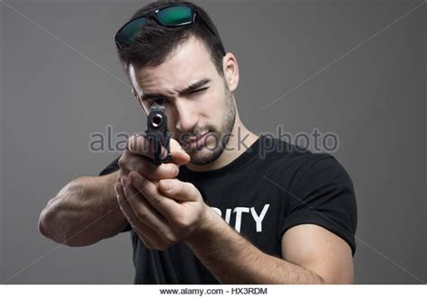 squinting one eye policeman aiming with pistol stock photos policeman aiming with pistol stock images