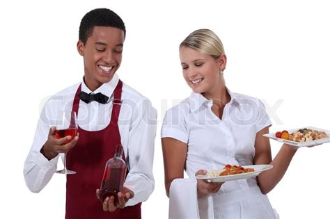 a wine waiter showing a bottle to a waitress stock photo colourbox