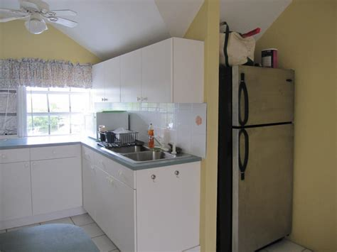 real estate tips kitchen area with white formica cabinets stainless steel fridge