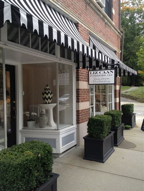 storefront awnings red brick black and white awnings black square planters
