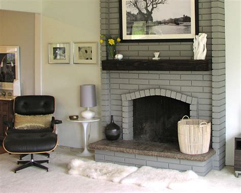 painted brick fireplace in a light gray with wood mantel in a contemporary setting