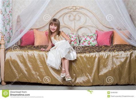 bed dress the girl in a beautiful dress is sitting on the bed