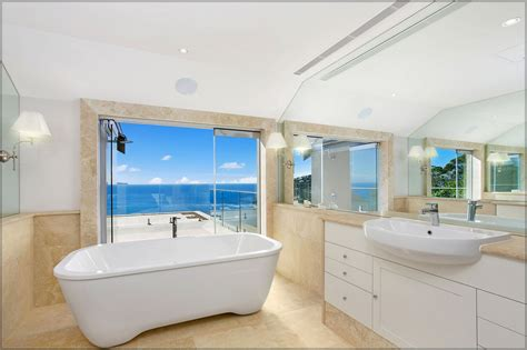 Modern style beach inspired bathroom design with large wall mirror and mounted lighting plus