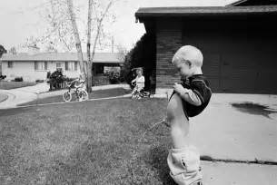 Funny black and white picture of boy peeing on neighbor s lawn as