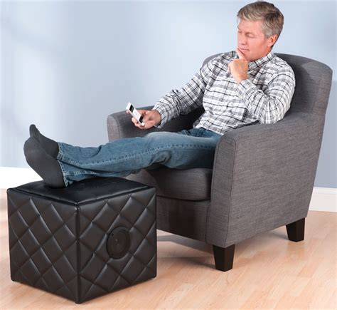 ottoman man relax by putting your feet up on a nice bluetooth speaker