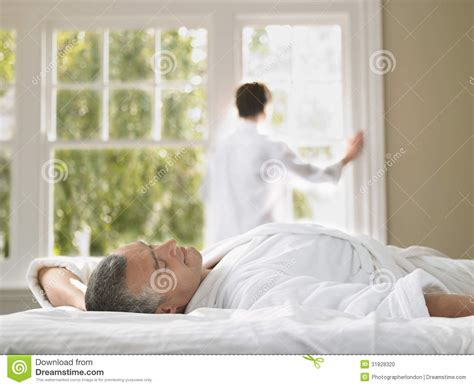 standing bed man lying in bed with woman standing at window stock photo