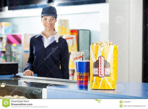 snacks on concession stand at cinema with worker stock