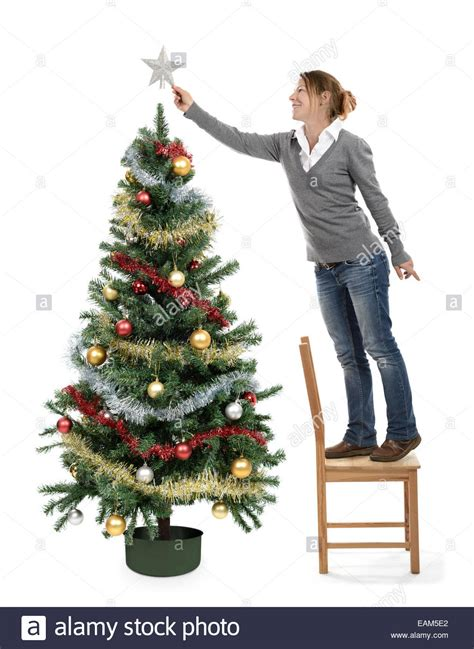 woman christmas tree decorating ornaments putting a star