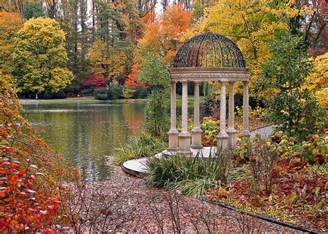 gazebo in autumn with fall foliage by large lake at