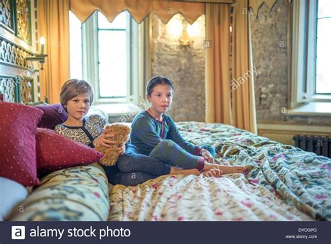 boys in bed two boys in onesies on the biggest hotel bed in europe at thornbury stock photo