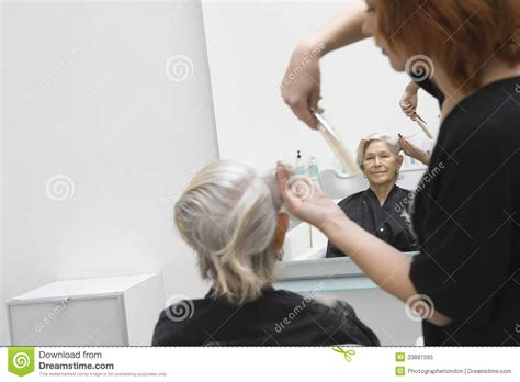 women haircutting in prison senior woman getting haircut in salon royalty free stock